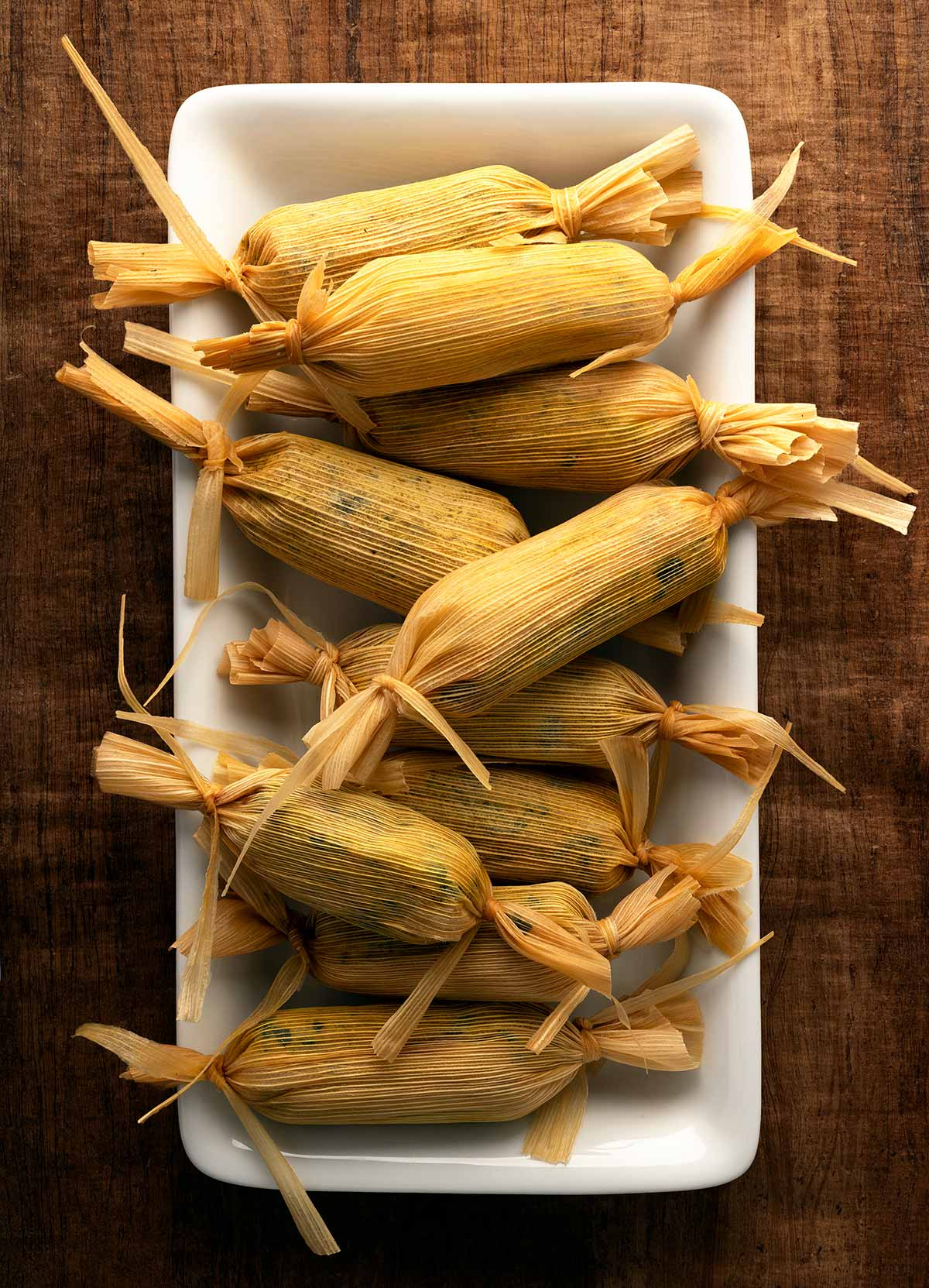 Chaya tamales in the husk on a plate