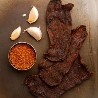 Smoked venison jerky with some of its main ingredients